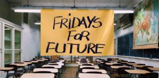 Aula baleira con cartaz de Fridays for Future diante da pizarra