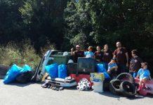 Participantes na limpeza simultánea de ríos con mostra de residuos retirados: neumáticos, electrodomésticos e outro lixo