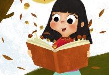 Nena cun libro aberto sobre o que caen follas dunha árbore en Outono
